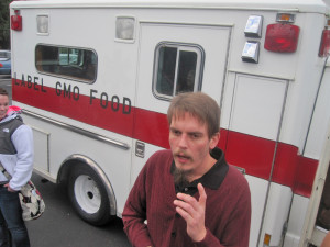 Chris McManus, signature coordinator for Initiative 522, pulls up to the state elections office in an ambulance.