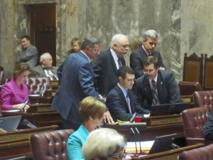 Republican senators huddle on the floor as votes are counted on the first of the education measures, the report-card bill.