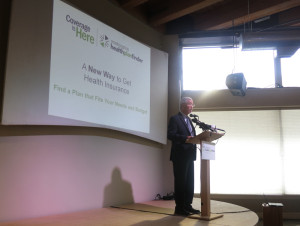 Health exchange director Richard Onizuka touts technological achievement at media event in Seattle Monday.