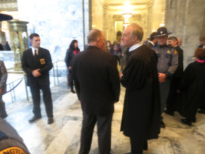 Justice James Johnson, the lone dissenting vote on the Supreme Court order, drew wild cheers on the House floor when he was introduced. Here he speaks with Senate Judiciary Chairman Mike Padden, R-Spokane, on the way out of the chamber.