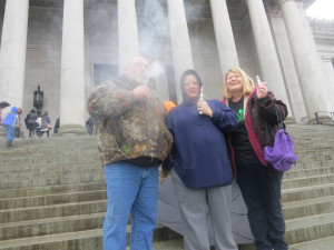 Dennis Hobart of Rainier, Geraldine Alvord of Buckley and Eva Hobart of Rainier take a 'vape break' on the Capitol steps Saturday.
