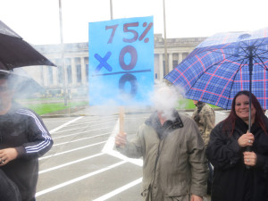 Vape-shop worker Jason Carnahan of Vancouver (behind cloud) carries a sign that makes a point about the 75-percent tax proposal.